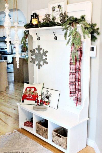 A space saving DIY Farmhouse Christmas hall tree decorated with cushions, greenery, a lantern and Christmas decor.