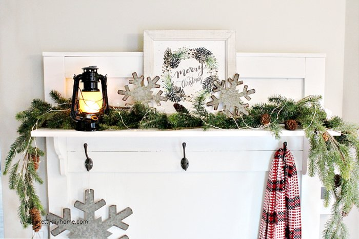 A farmhouse Christmas entry shelf decorated with galvanized snowflakes a lantern and merry Christmas sign.