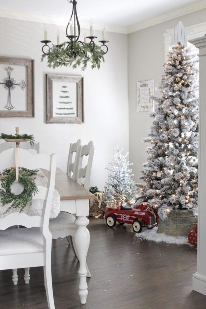 White farmhouse Christmas decor with a white farmhouse table, white Christmas tree and pretty vintage child's riding toy .