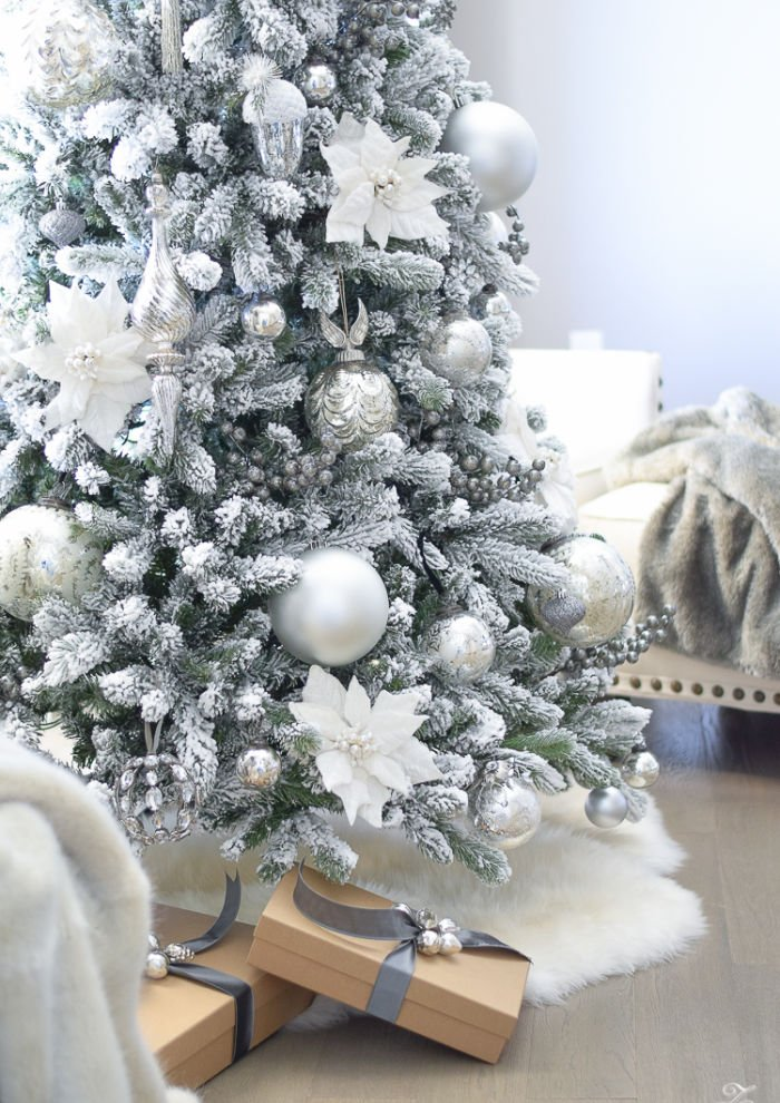 Large flocked Christmas tree with All White Christmas Decorations