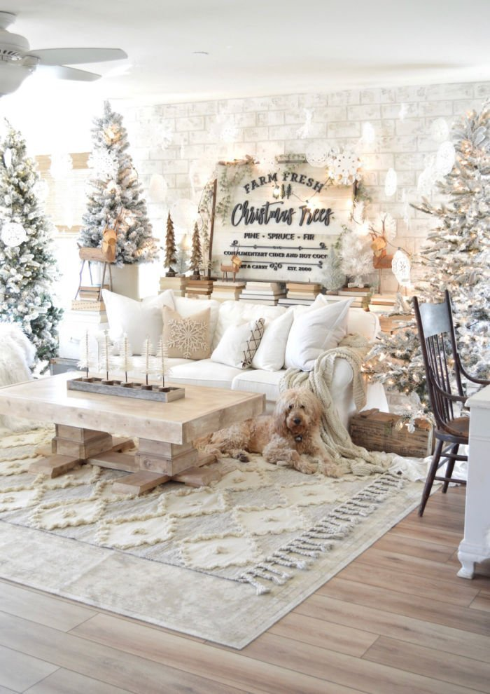 Living decorated with lots of white flocked Christmas tree, white cushions and snowflakes.