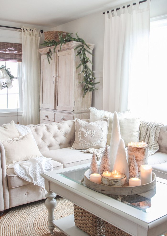 A Christmas living room decorated in white decor with a nice white armoire in the background.