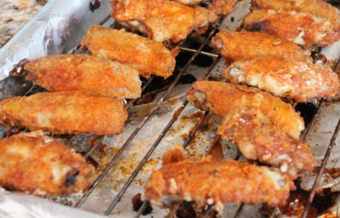 Golden brown baked chicken wings, on racks coming right out of the oven.