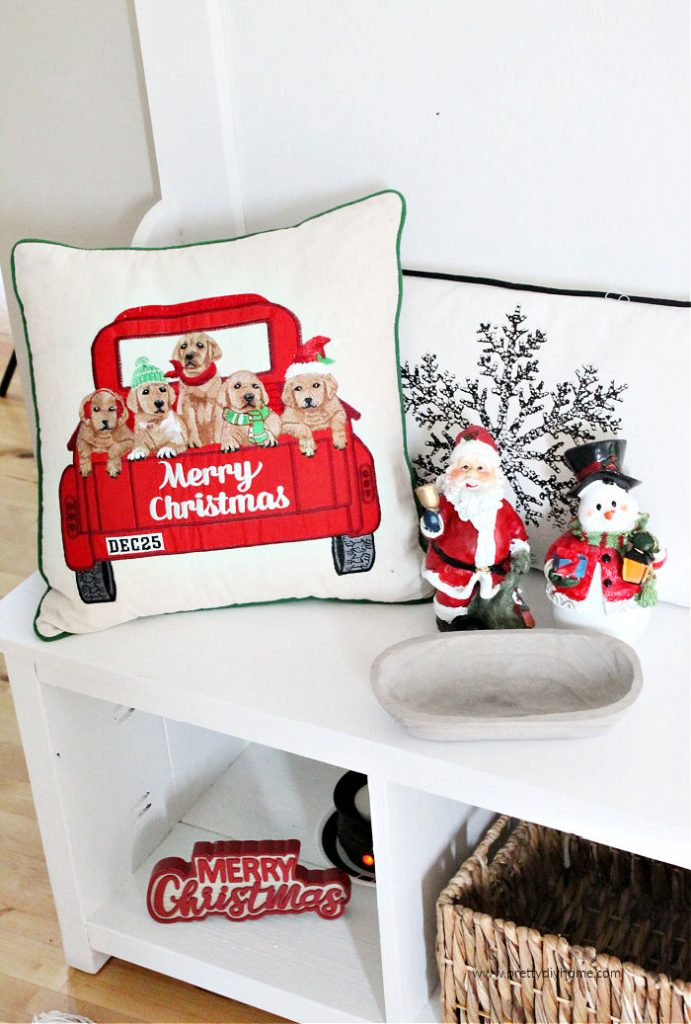 A DIY farmhouse hall tree decorated with cushions and baskets for Christmas.
