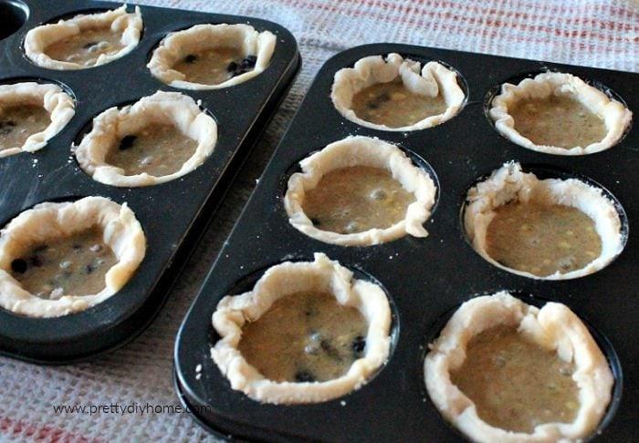 Filling tart tins with butter tart filling so that each tart is 2/3 full.