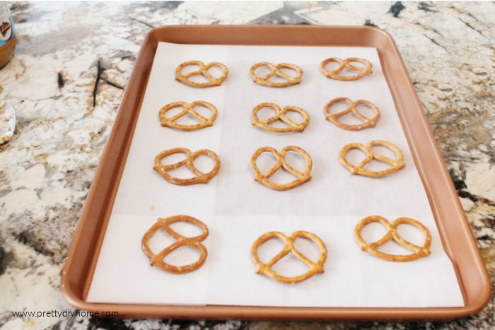A cookie sheet lined with pretzels for making no bake chocolate peanut butter budget pretzel treats.