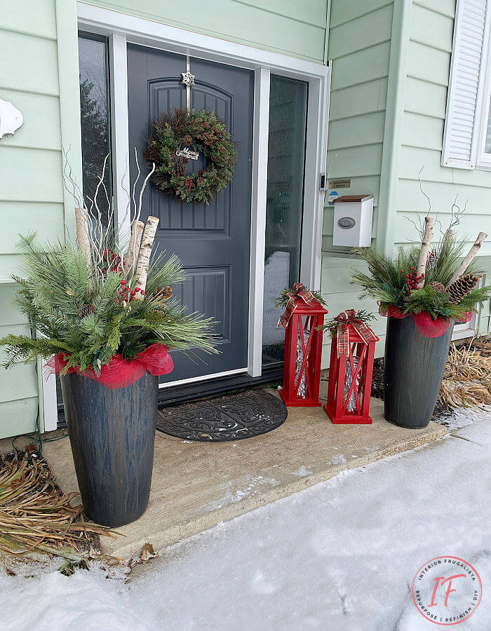 Two large red DIY Christmas lanterns sitting on the front porch for the holidays.