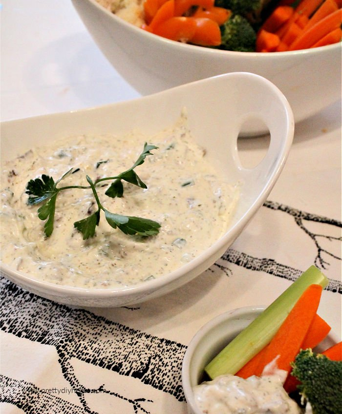 A large bowl of homemade ranch dip served with fresh celery, carrots, brocoli and cauliflower.