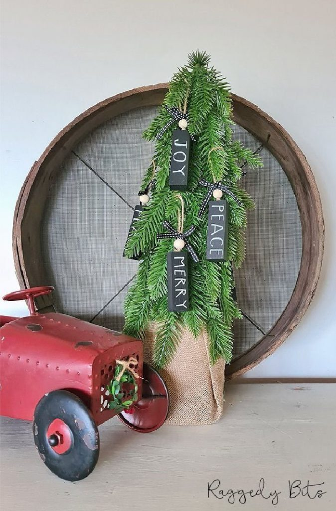 DIY Black and White Christmas Decorations hanging on a miniature tree with a vintage red truck.