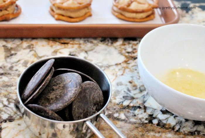 A cup of Belgian melting wafers and a bowl of butter for making chocolate coating