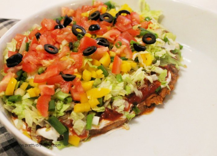Seven layer dip with refried beans, cheese and vegetables in pretty layers. The dip is layered into a bowl so the taco chips can be tossed in beside.