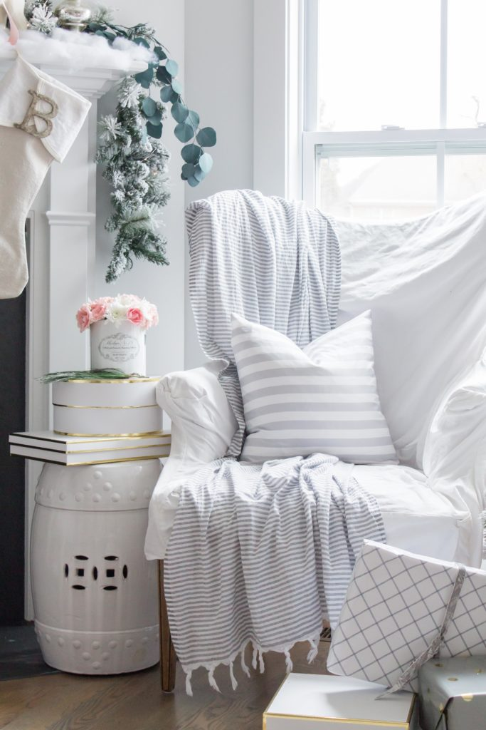 A white covered armchair with white throw, and white Christmas decor