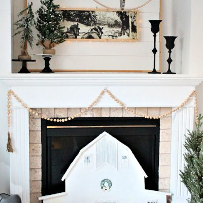 Farmhouse Style Christmas Mantel featuring a DIY large barn, horse and sleigh artwork and DIY farmhouse wood bead garland.
