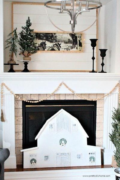 Farmhouse Style Christmas Mantel featuring a DIY large barn, horse and sleigh artwork and DIY farmhouse wood bead garland.