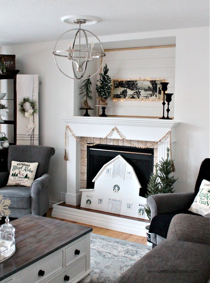 Living room decorated for Christmas in neutral farmhouse style including a Christmas mantel with large DIY barn