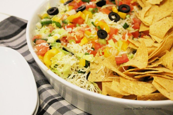A large platter of seven layer bean dip with taco chips in a bowl.