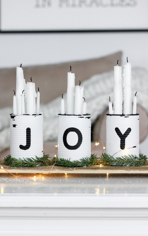 Simple centerpiece for Christmas with white cans and white candles.
