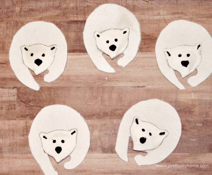 Five fabric polar bear rustic DIY Christmas ornaments in white with cut black felt noses.