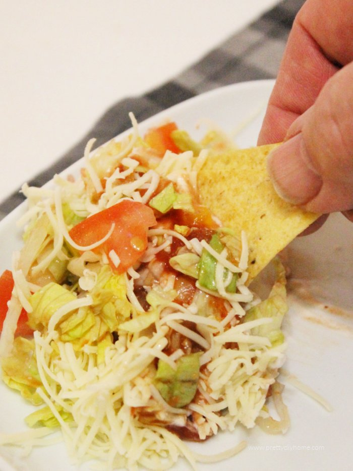 Seven layer dip with refried beans, cheese and vegetables being served with taco chips.