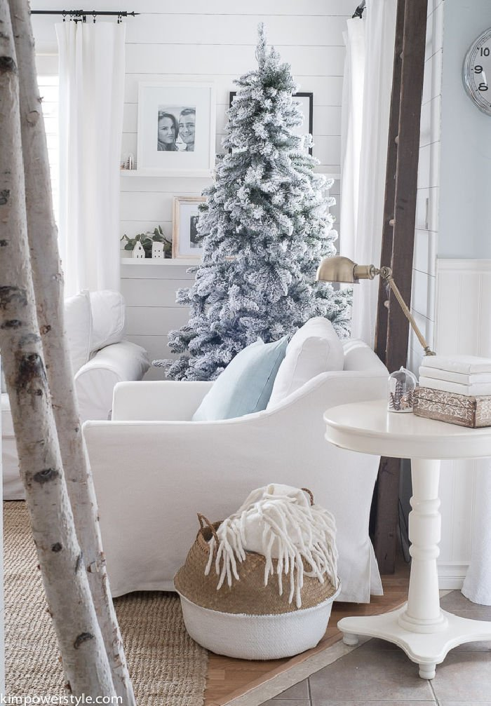 Winter wonderland family room decorated in White Christmas decorations with white furniture and white couch covers.
