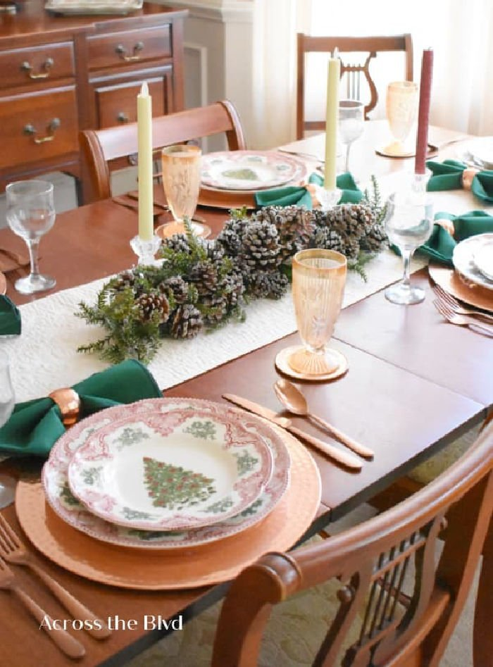 Traditional Christmas table setting with vintage Christmas plates and peach goblets.