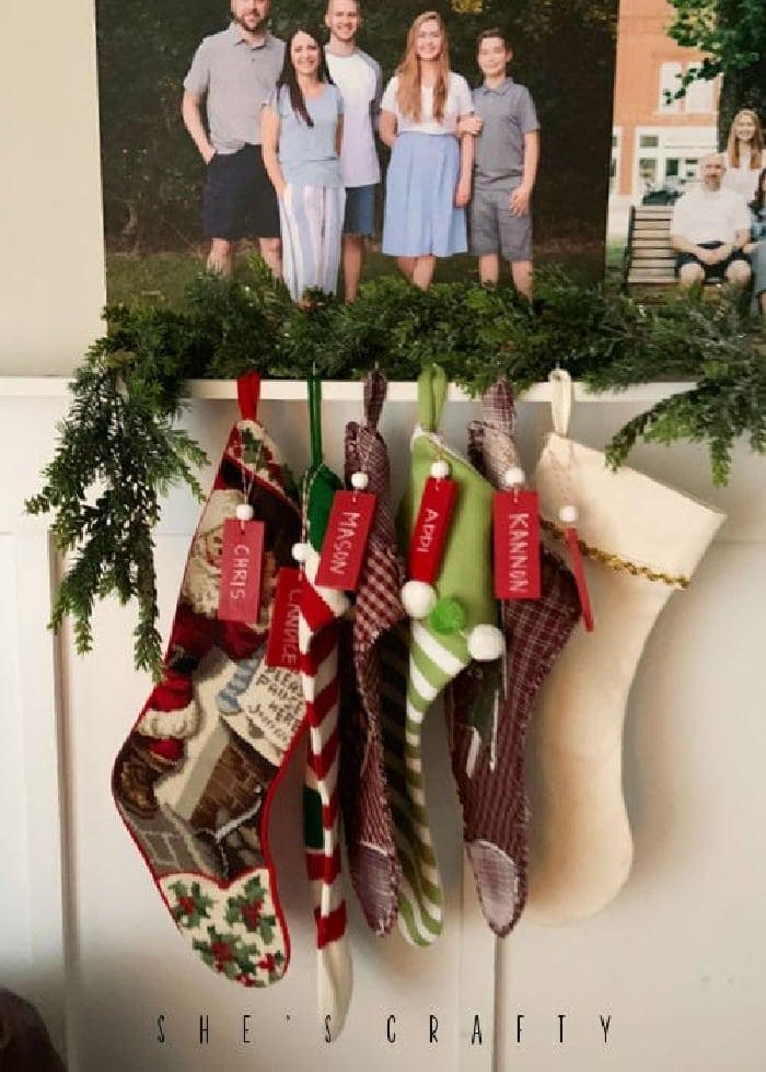 DIY Stocking Name Tags hanging with stockings on a Christmas shelf.