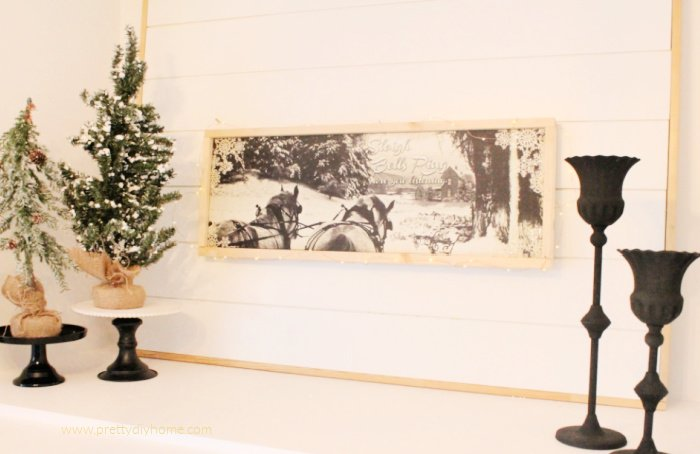 Sleighbells ring artwork in neutral colours showing two work horses pulling a large sleigh.