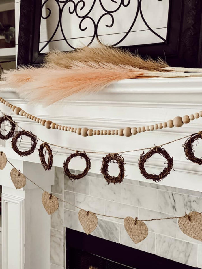 A white fireplace decorated with neutral coloured Valentine banners, including farmhouse beads, and burlap hearts.