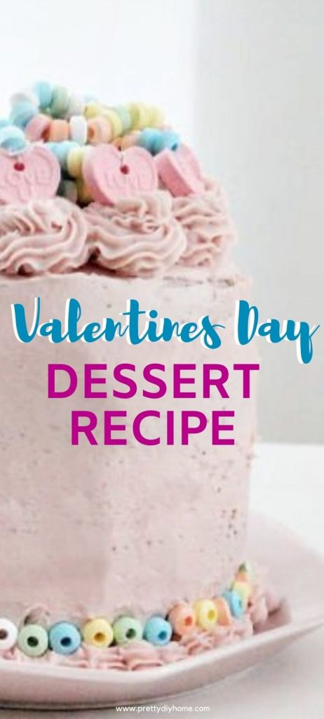 A large chocolate cake covered with smooth soft pink strawberry cream cheese icing and topped with icing swirls and Valentine candy bracelets.