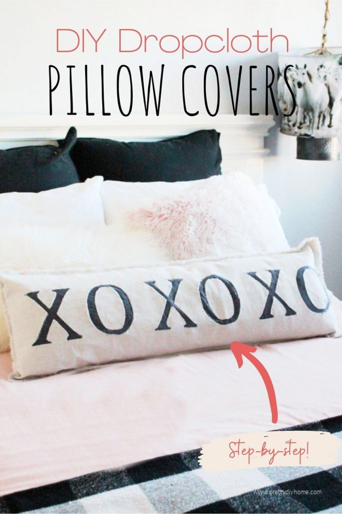 DIY drop cloth farmhouse pillows with large XO letter appliqued on the front. The pillow sits across the front of a farmhouse bed with pink bedding and fur cushions.