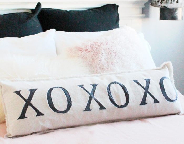 A farmhouse style bed with pink bedding and an appliqued XO farmhouse pillow.