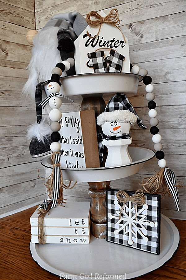 A handmade three tiered farmhouse tray with wooden block decor, snowmen, and a black white and taupe farmhouse beads.