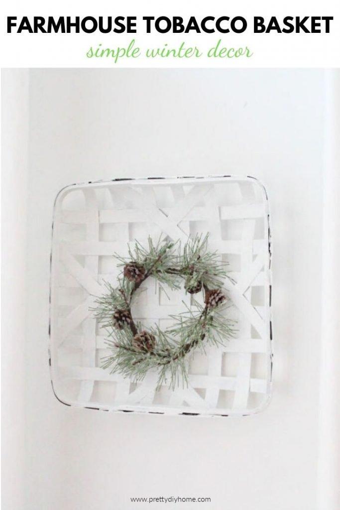 A DIY white tobacco basket made into a farmhouse winter wreath using a tiny green spruce wreath.