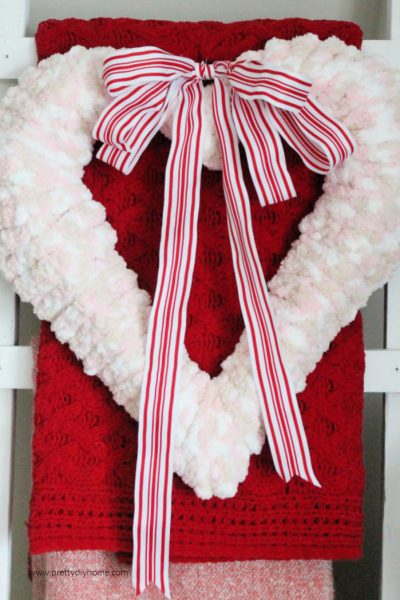 Gorgeous pink wool Farmhouse Valentine wreath with grain sack red and white ribbon. The large wreath is hanging on a farmhouse ladder.