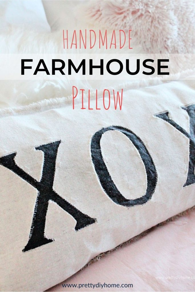 A large handmade farmhouse pillow with XO letters appliqued on the front. The cushion is sitting on a bed with pink bedding in a modern farmhouse style.