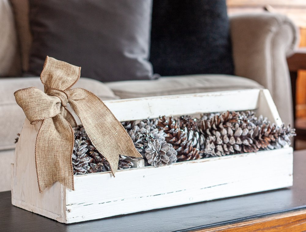 A minimalist vintage toolbox in white with a burlap bow filled with white frosted pinecones for winter decorating.