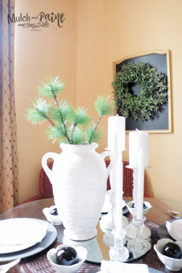 A large ceramic vase makeover in white on a table with candles.