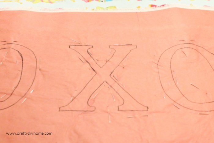 X and O letter on freezer paper with lots of sewing pins holding down all the letter edging.