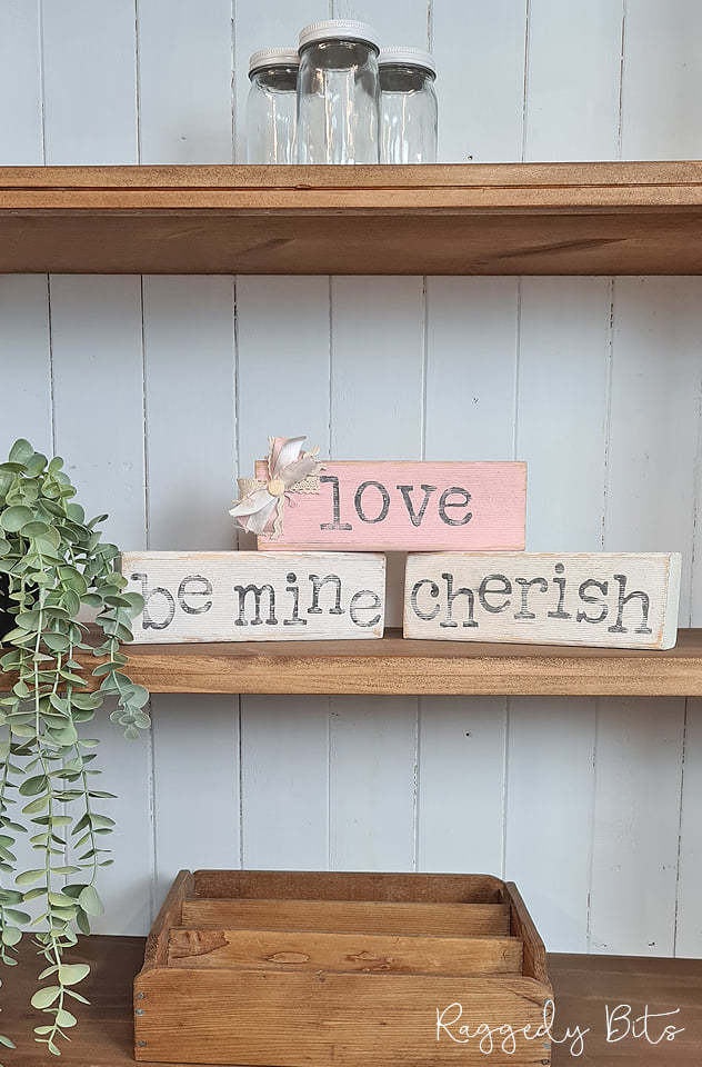A shelf with DIY stamped farmhouse signs that say love, be mine and cherish.