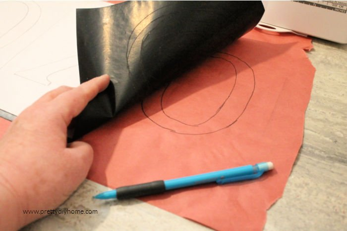 Transferring a pattern onto freezer paper using carbon paper.