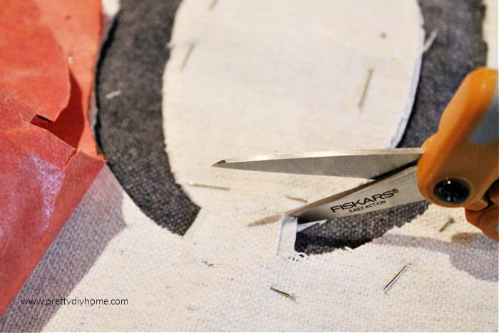 Using scissors snipping out the little bits of fabric that was holding the center piece of the letter O