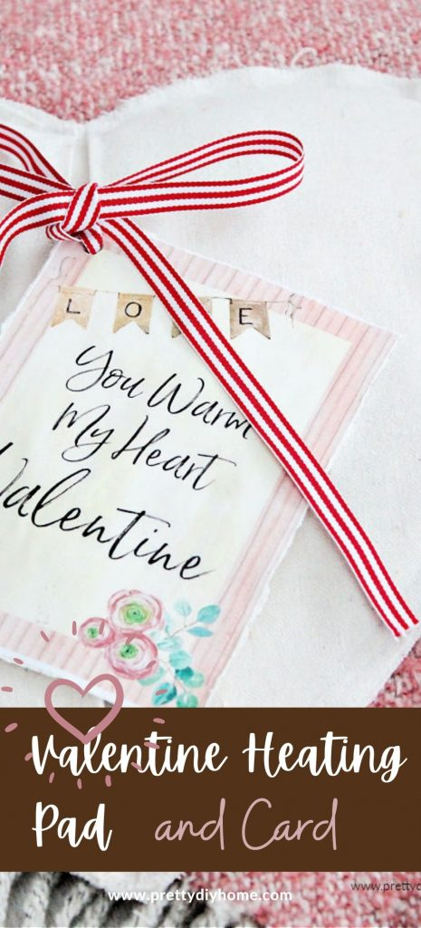 A DIY Valentine shaped heating pad made out of drop cloth and grain sack ribbon. There is a pink feminine Valentine card on the front that says you warm my heart Valentine.