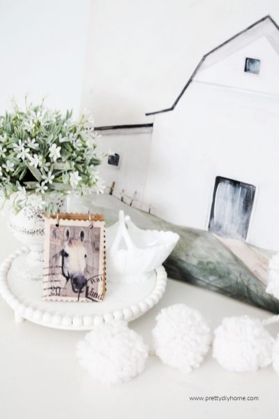 A white DIY wood table riser with white bead edging, holding milk glass, a small flower plant and booklet with a horse cover. Surrounded by a snowball garland and white barn sign backdrop.