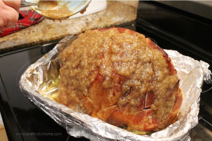 Removing an oven baked ham and topping it with apple brown sugar glaze before placing it back in the oven.