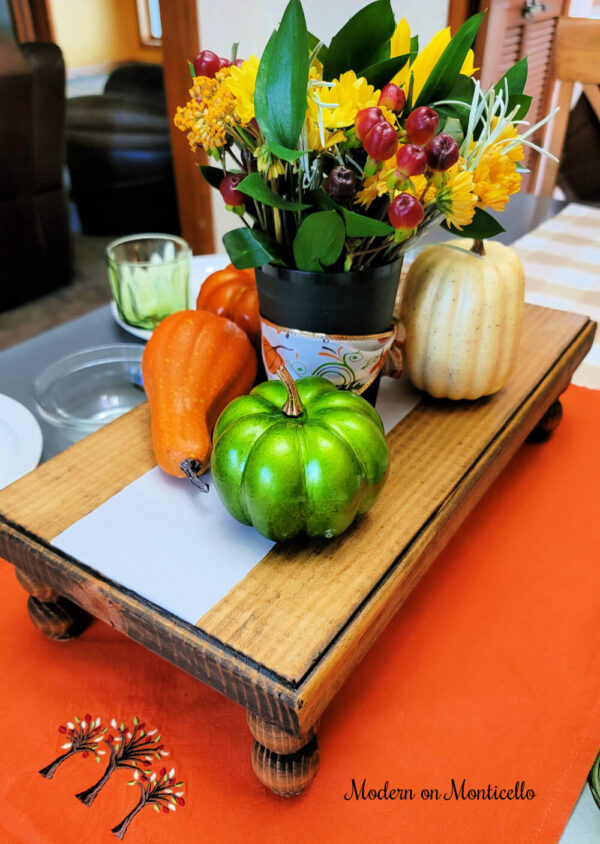Hand made decorated wood tray on a dining room. This wooden tray is in soft brown stain with a grain sack stripe down the middle