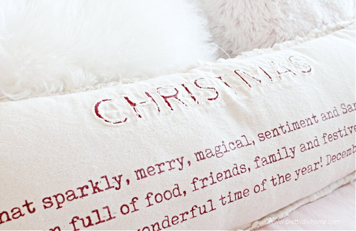 Large farmhouse cushion with applique lettering and painted saying for Christmas. Cushion used as inspiration for a handmade farmhouse pillow.