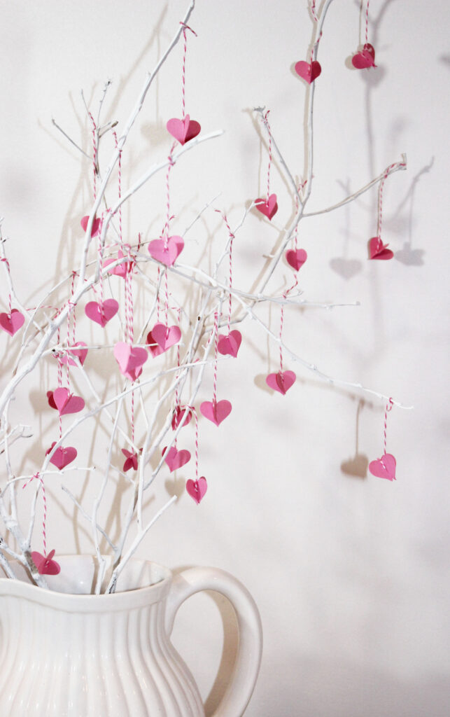 White branch with tiny pink valentines hanging from it.