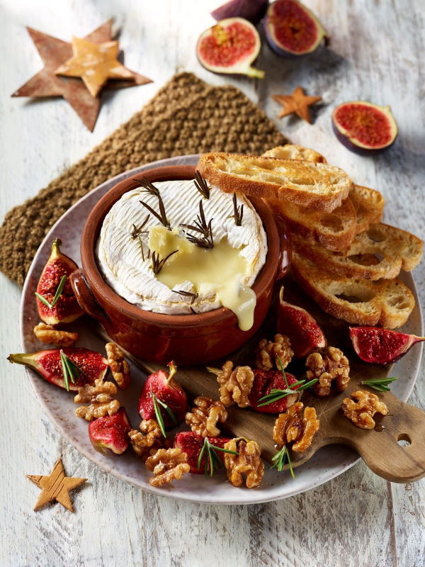 Camembert figs and walnuts on a wood cutting board. A homemade appetizer recipe.