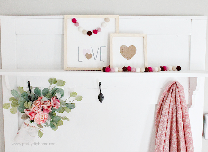 Two wood Valentines with white background, and natural wood frame. One sign says Love the other one has a layered brown Valentine. Both pictures are draped with pretty felt ball garland.