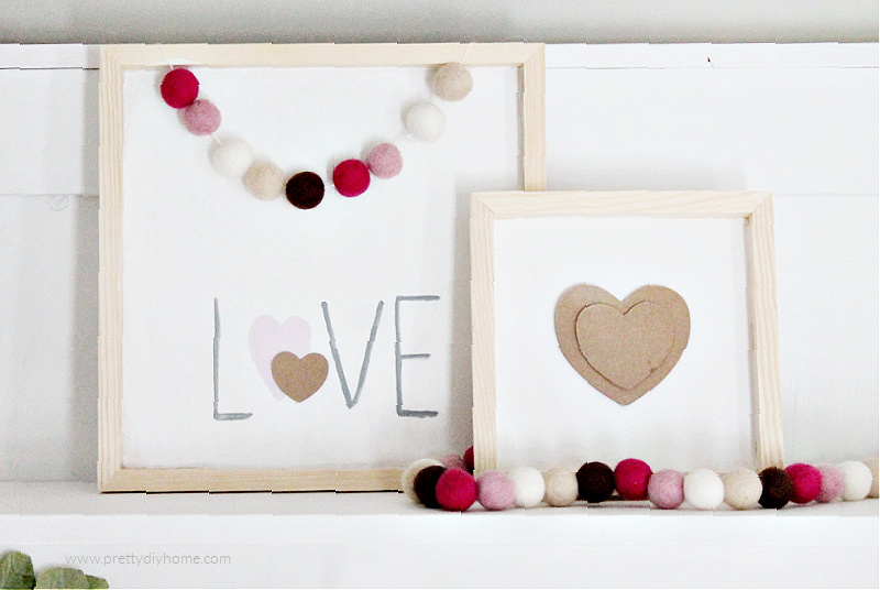 Two farmhouse DIY Valentine signs with white backgrounds and natural wood frames, one says love and the second one a layered cardboard heart. Both signs are accessorized with pretty felt balls in shades of pink and brown.